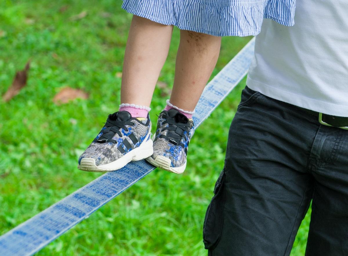 Eine Slackline für Kinder bietet Spaß im Park und ist außerdem ein tolles Gartenspielzeug.