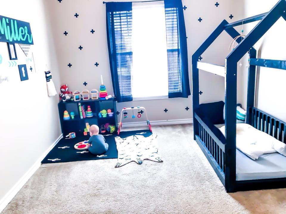 Baby im Montessori Babyzimmer mit Hausbett und Spielbereich