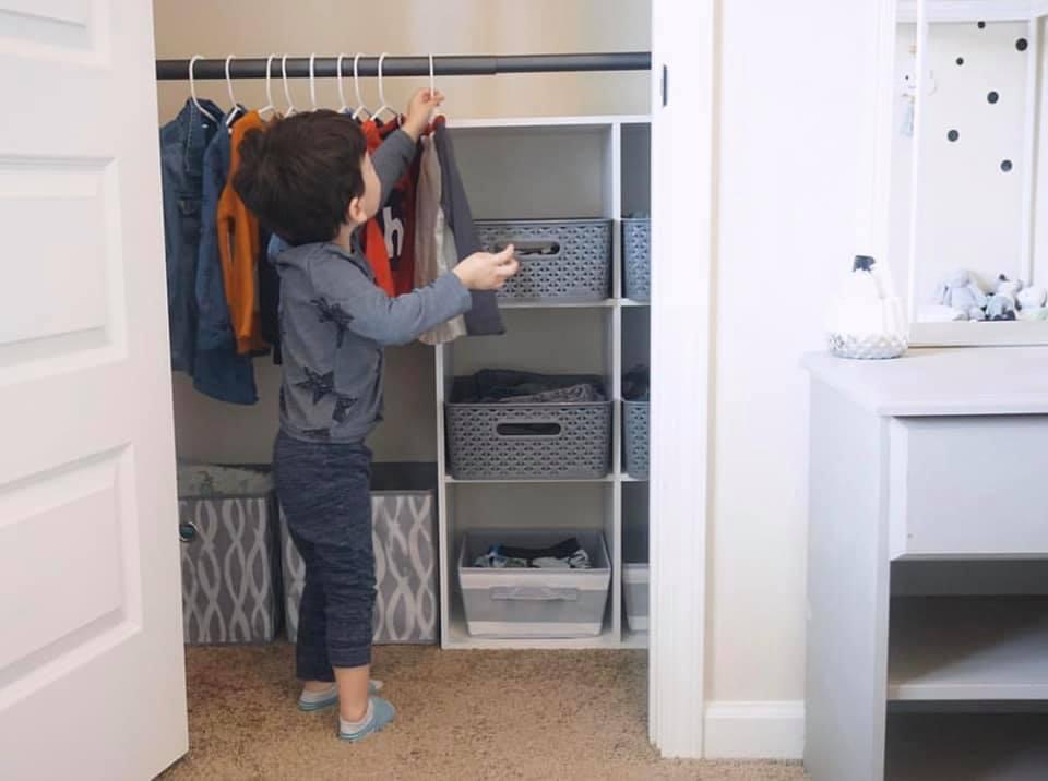 Kleinkind wählt Kleidung aus dem Montessori Kleiderschrank aus