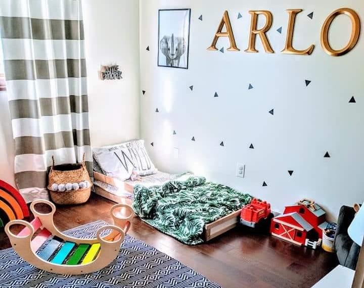Kinderzimmer mit Bodenbett und Schriftzug Arlo an der Wand