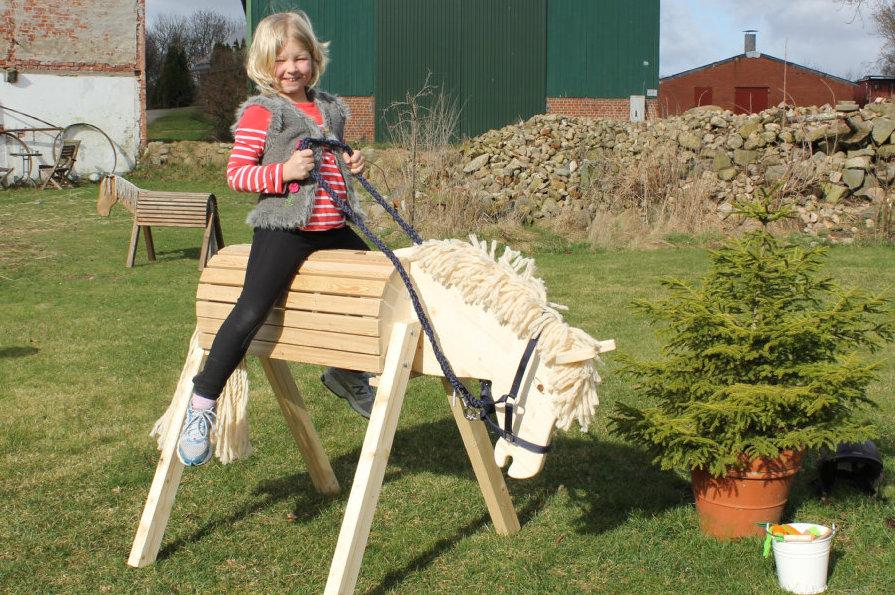 Kind reitet auf Holzpferd im Garten
