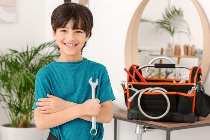 Junge mit echtem Werkzeug und Kinder-Werkzeugkasten