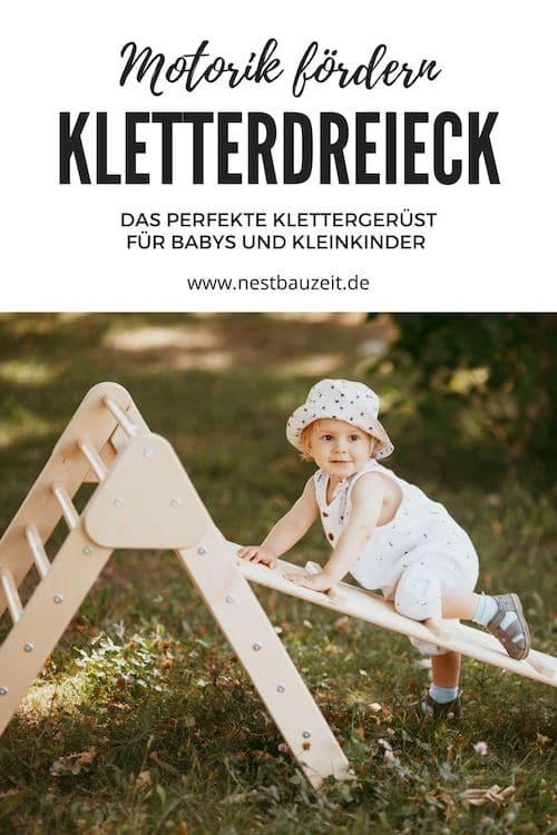 Kleinkind klettert auf dem Kletterdreieck nach Pikler-Art.