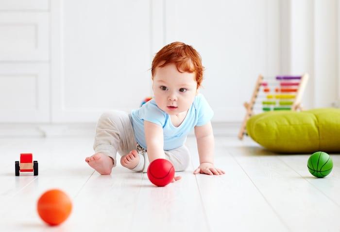 Baby krabbelt hinter Bällen her
