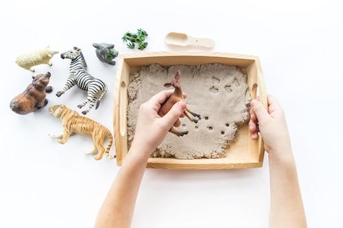 Montessori Spielzeug: Kind spielt mit Tierfiguren und kinetischem Sand