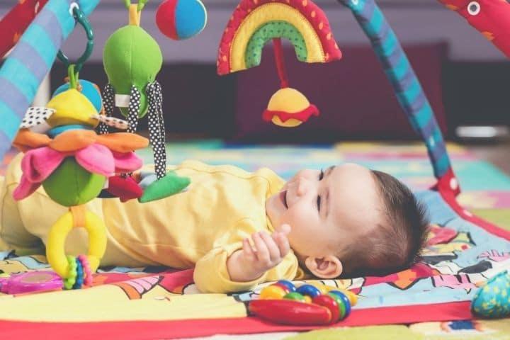 Baby liegt unter dem Spielbogen