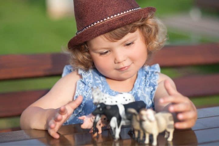 Kind spielt mit Tierfiguren