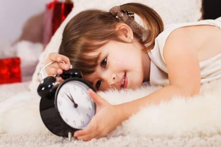 Mädchen mit Kinderwecker im Bett
